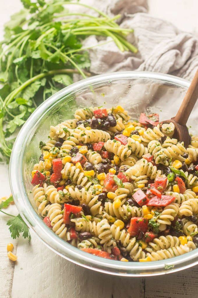 Bowl of Southwest Pasta Salad with Wooden Spoon, Bunch of Cilantro in the Background