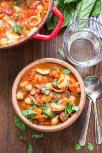 Bowl of Vegan Minestrone Soup with Spoons and Water Glass