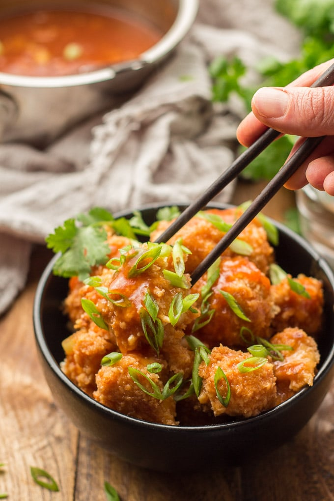 Hand Holding a Pair of Chopsticks Grabbing a Cauliflower Floret From a Bowl of Cauliflower Manchurian