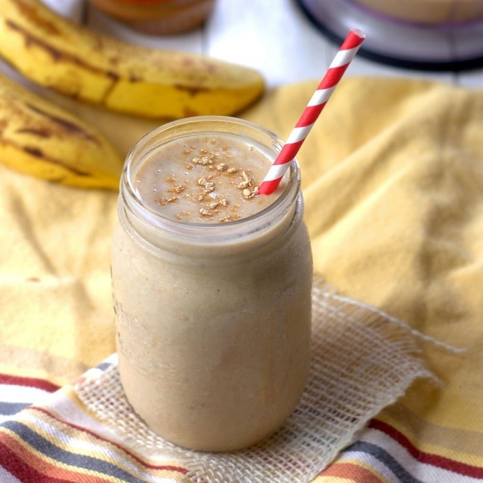 Peanut Butter Maca Smoothie in a Glass with Bananas in the Background