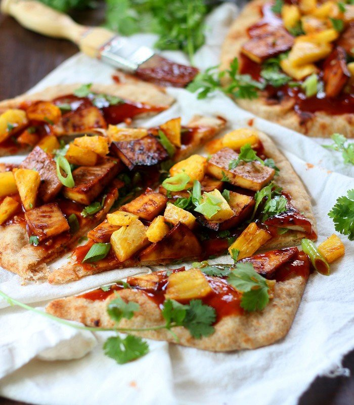 Close Up of a Sliced Naan Pizza Topped with Tofu, Pineapple, and Herbs