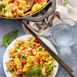 Pineapple Fried Rice on a Plate with Water Glass, Chopsticks and Skillet on a Blue Background
