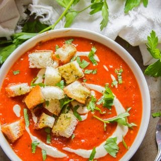 Overhead View of a Bowl of Overhead View of a Bowl of Roasted Red Pepper Soup with Garlic Bread Croutons with Spoon on the Side with Napkin and Parsley
