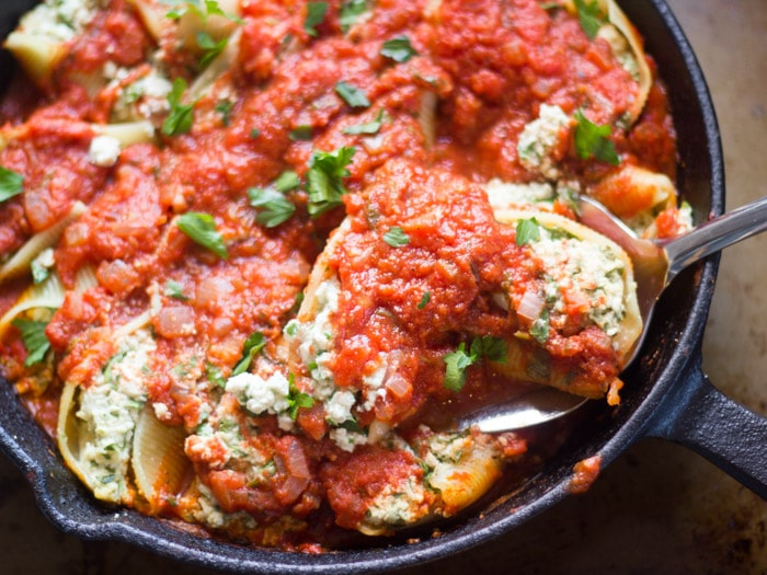 Vegan Stuffed Shells Florentine in a Skillet with Serving Spoon