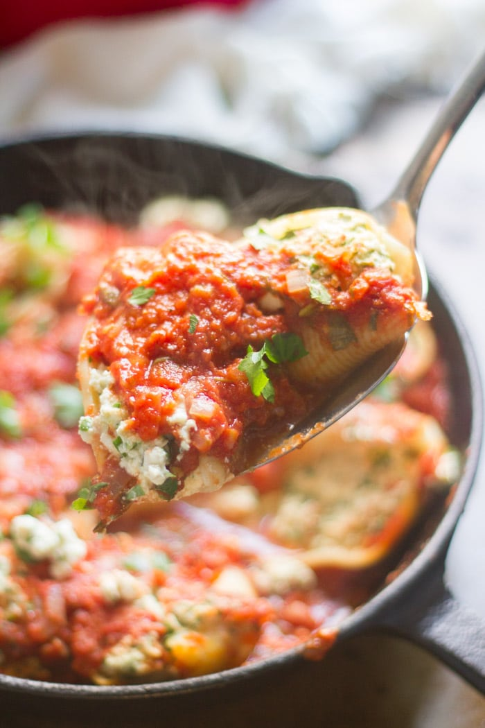 Close Up of Two Vegan Stuffed Shells Florentine in a Serving Spoon with Skillet in the Background