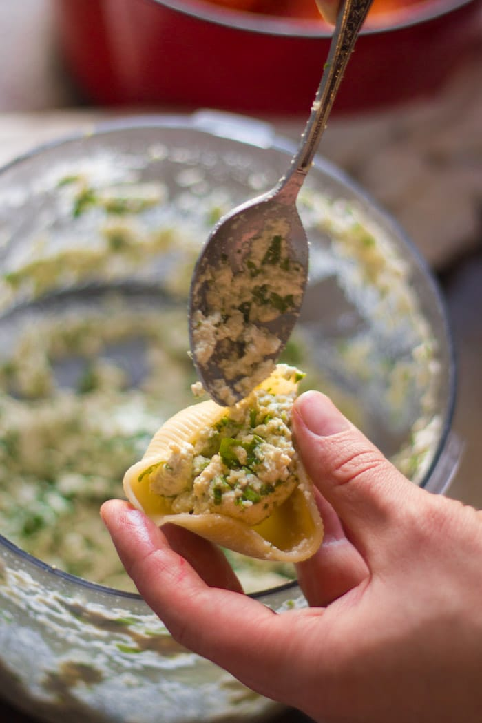 Hand Spooning Vegan Ricotta into a Pasta Shell to Make Vegan Stuffed Shells Florentine