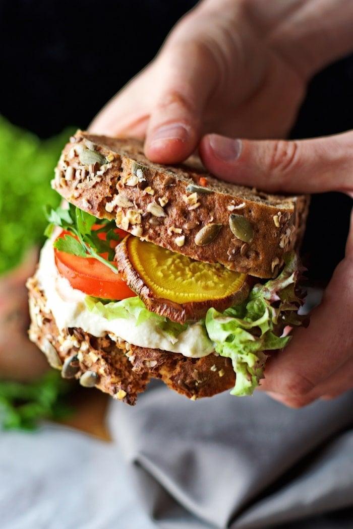 Hands Holding a Golden Beet Sandwich