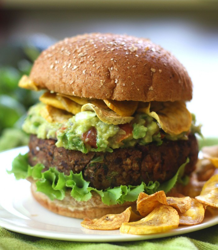 Close Up of a Black Bean Burger Topped with Guacamole and Plantain Chips