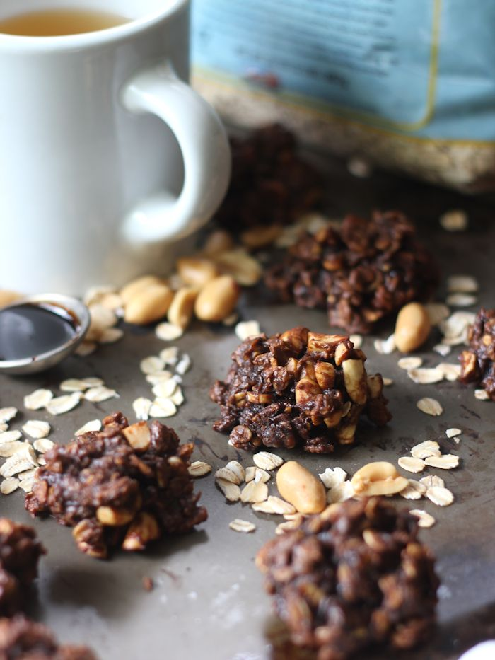 Breakfast Cookies on a Metal Surface Surrounded By Oats and Peanuts, Coffee Cup in the Background