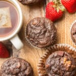 Vegan Chocolate Zucchini Muffins, a Cup of Tea, and Strawberries Arranged on a Wooden Surface