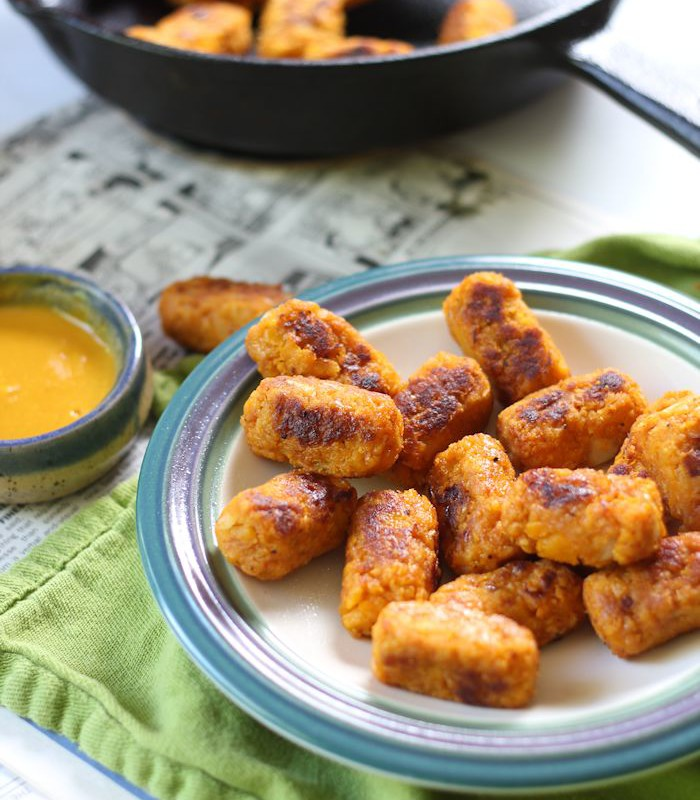 Plate of Butternut Squash Tots with Skillet and Dish of Mustard Sauce in the Background