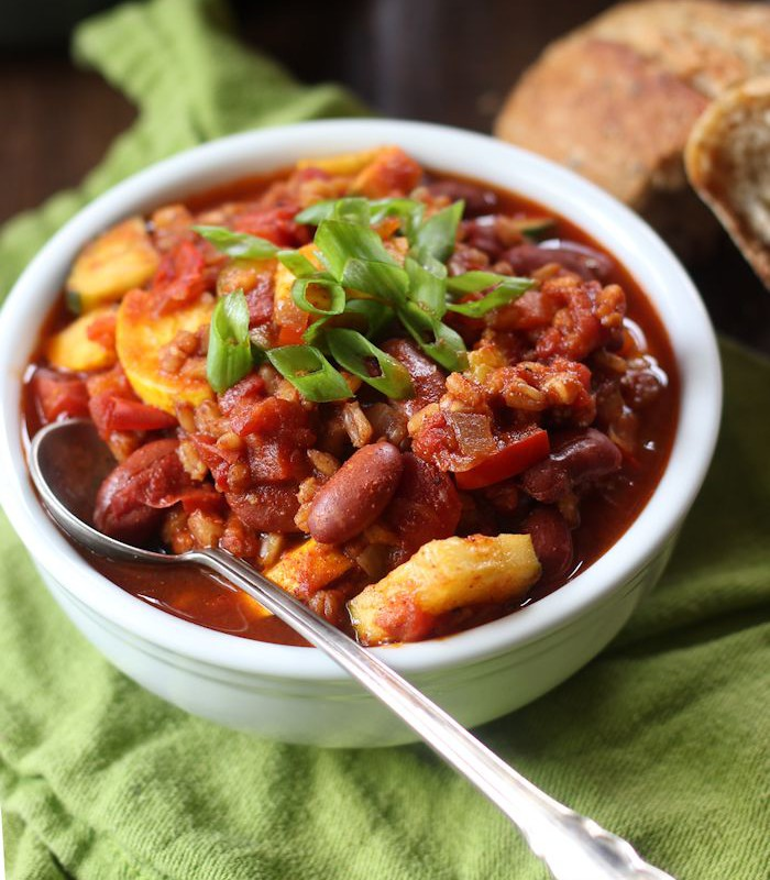 Bowl of Farro Chili with Spoon, Bread Chunks in the Background