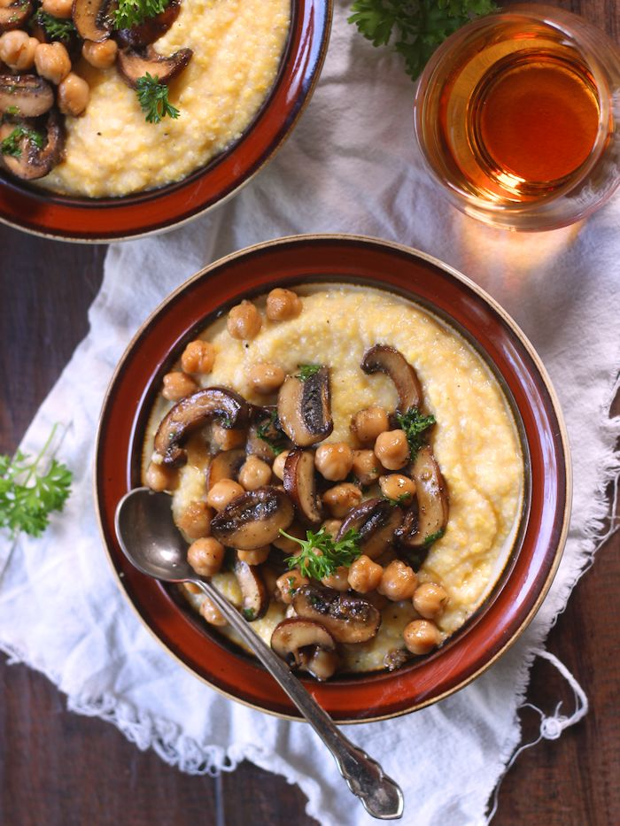 Overhead View of a Bowl of Chickpea Mushroom Marsala and Polenta Sitting on a White Cloth with Glass of Liquor