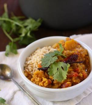 Bowl of Pumpkin Dal and Rice Topped with Fresh Cilantro, Spoon on the Side