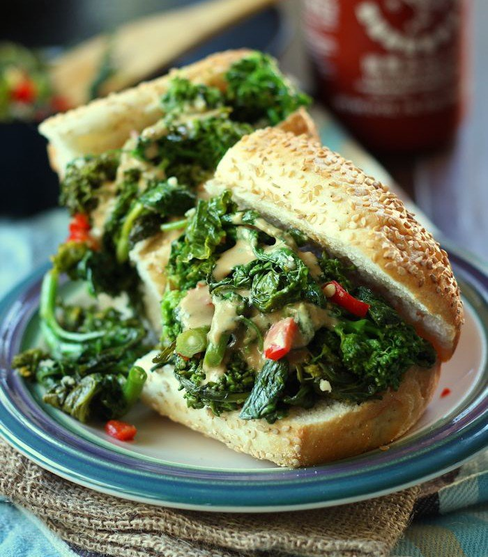 Close Up of Two Halves of a Broccoli Rabe Sandwich on a Plate