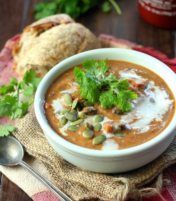 Bowl of Pumpkin Black Bean Soup  Topped with Cilantro and Pumpkin Seeds, Bread and Spoon on the Side