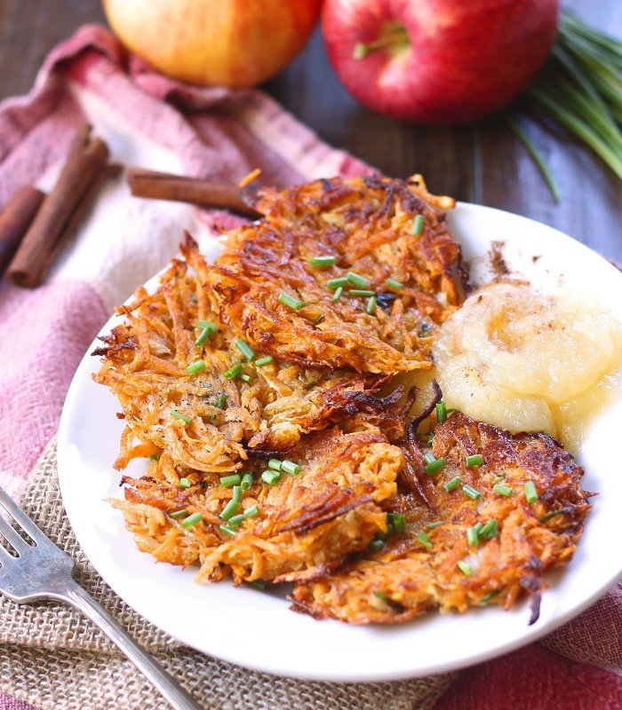 Sweet Potato Latkes on a Plate with Applesauce, Apples and Cinnamon Sticks in the Background