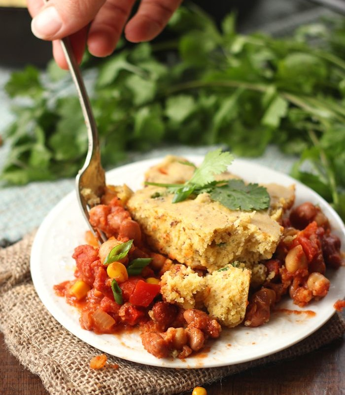 Hand with Fork Digging into a Slice of Vegan Tamale Pie on a Plate