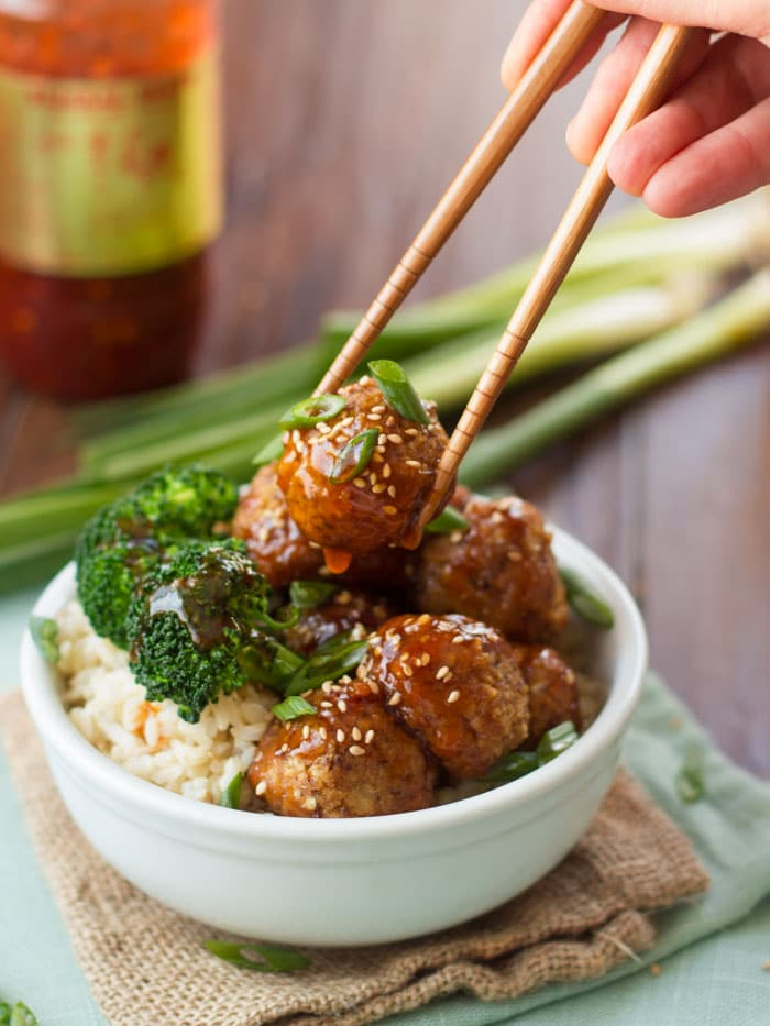 Pair of Chopsticks Grabbing a Tofu Meatball from a Bowl