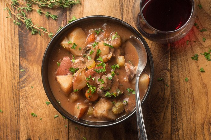 Bowl of Vegan Beef Stew with Spoon and Wine Glass