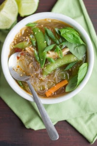 Overhead View of a Bowl of Glass Noodle Soup with Spoon on Green Fabric