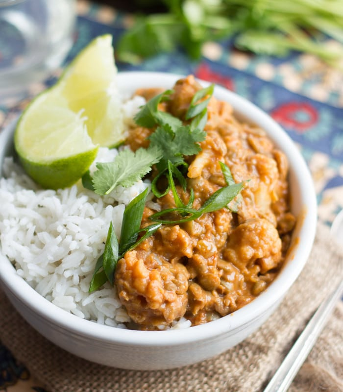 Bowl of Cauliflower & Lentil Curry with Rice, Lime Wedges, Scallions and Fresh Cilantro