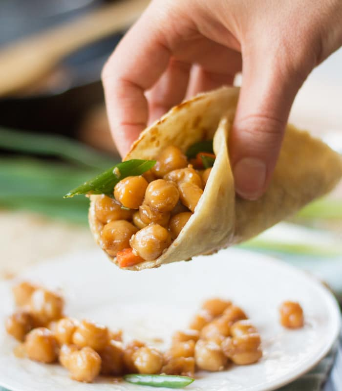 Hand Holding a Pancake Filled with Peking Chickpeas