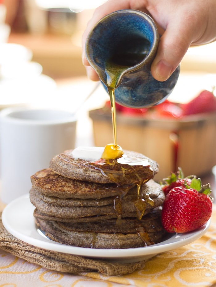Hand Pouring Maple Syrup Over a Stack of Vegan Buckwheat Pancakes