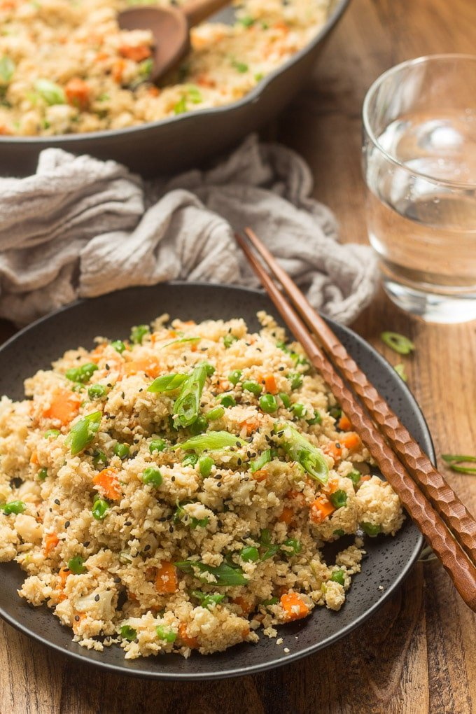 Plate of Cauliflower Fried Rice with Skillet, Tea Towel, and Water Glass in the Background