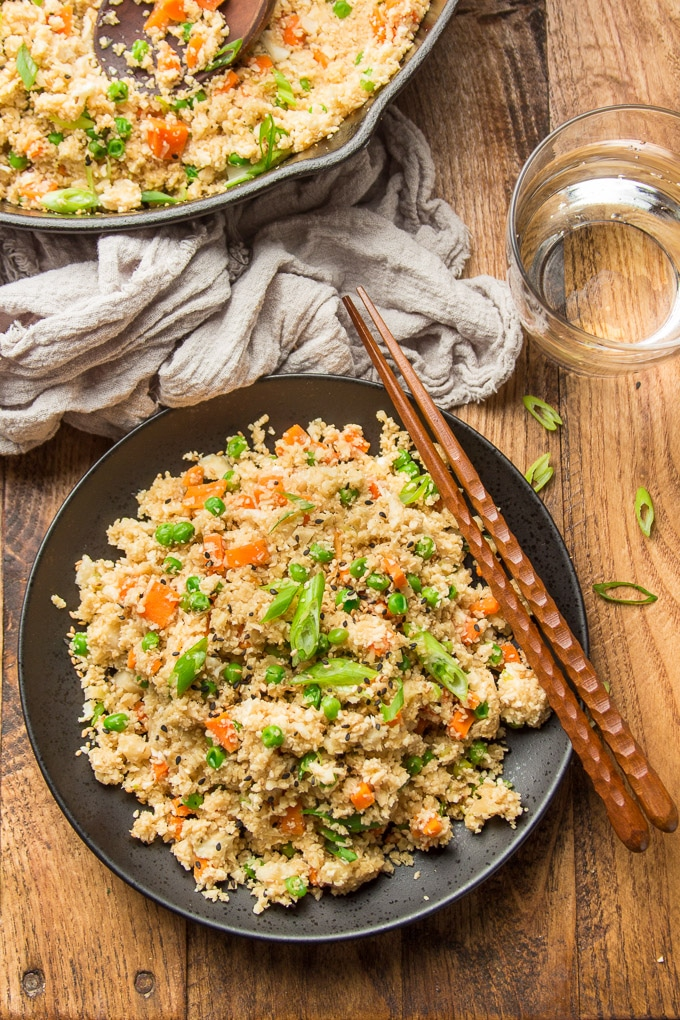 Wooden Table Set with Skillet, Water Glass, and a Plate of Cauliflower Fried Rice