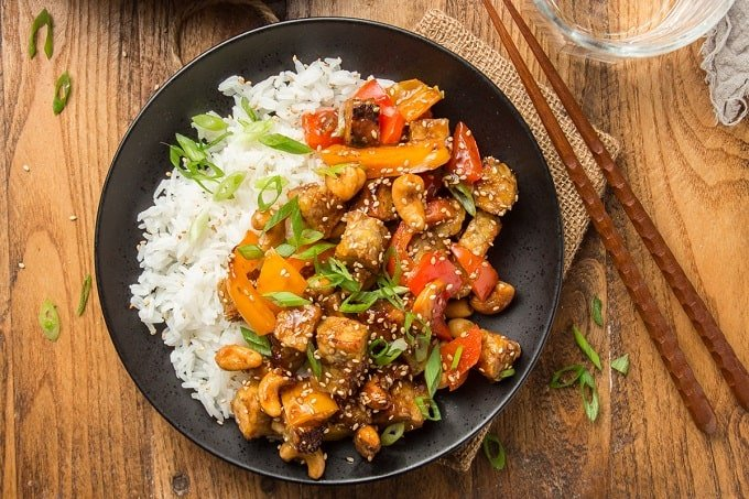 Plate of Tempeh Stir-Fry and Rice on a Wooden Surface with Chopsticks on the Side
