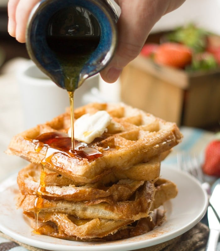 Hand Pouring Maple Syrup Over a Stack of Vegan French Toast Waffles