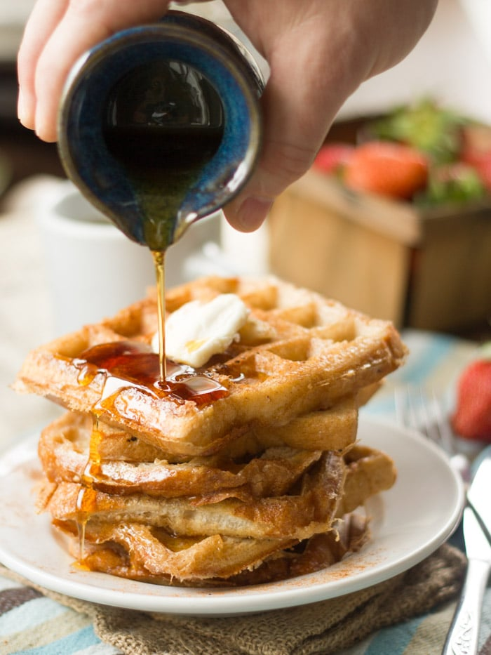 Stack of Vegan French Toast Waffles on a Plate with Syrup Being Drizzled on Top