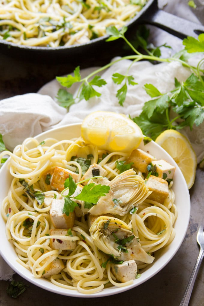 Bowl of Tofu and Artichoke Scampi with Fresh Parsley and Lemon Wedges