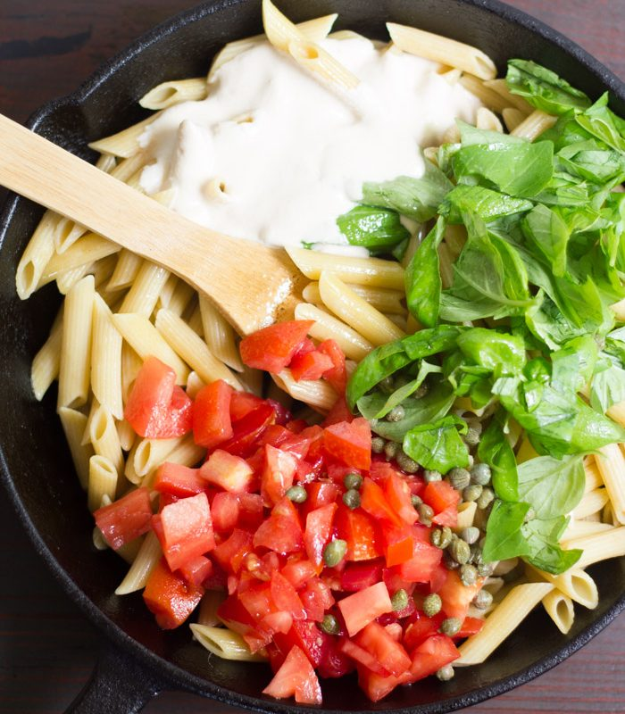 Ingredients for Creamy Vegan Tomato Basil Pasta in a Skillet with a Wooden Spoon