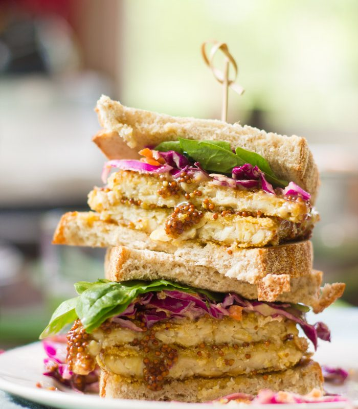 Two Halves of a Maple Dijon Tempeh Sandwich Stacked on a Plate
