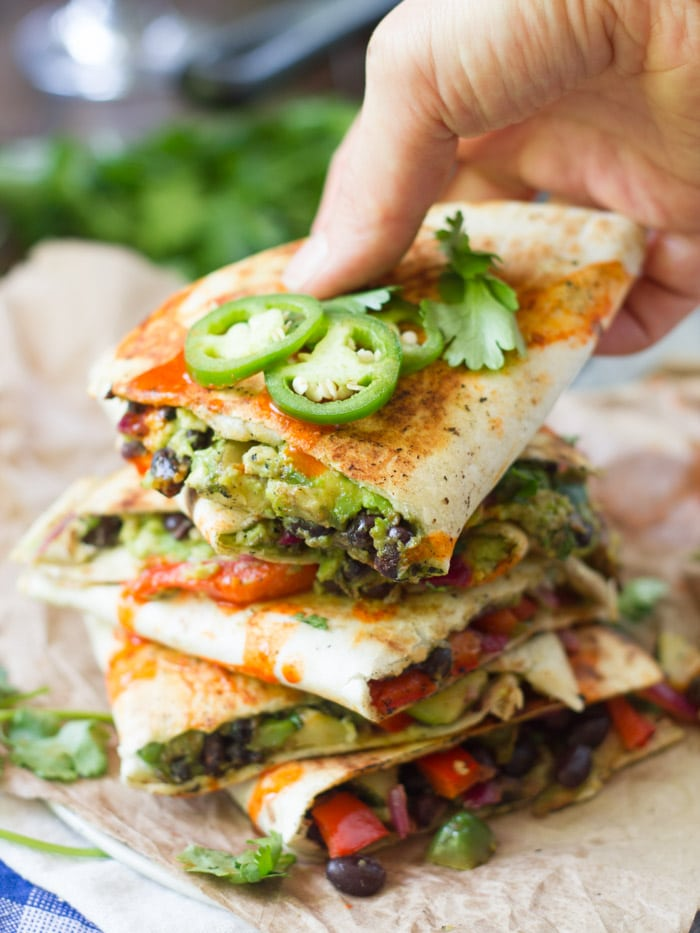 Hand Grabbing a Vegan Avocado Quesadilla from a Stack