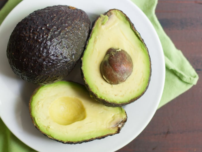Two Avocados on a Plate, One Whole, and One Cut in Half