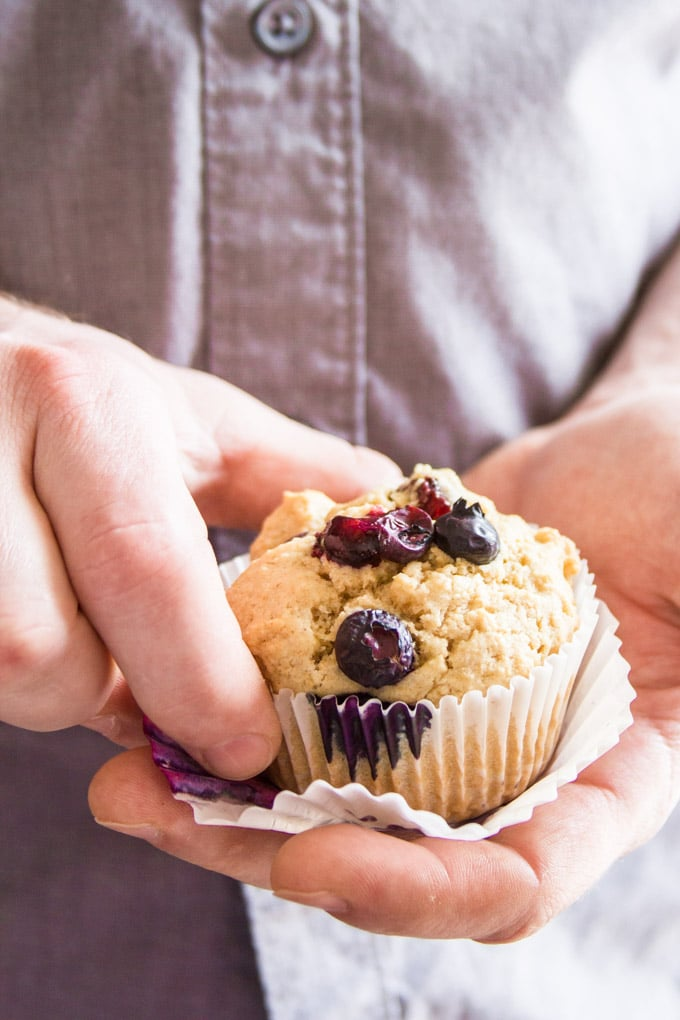 Pair of Hands Holding a Single Vegan Blueberry Muffins