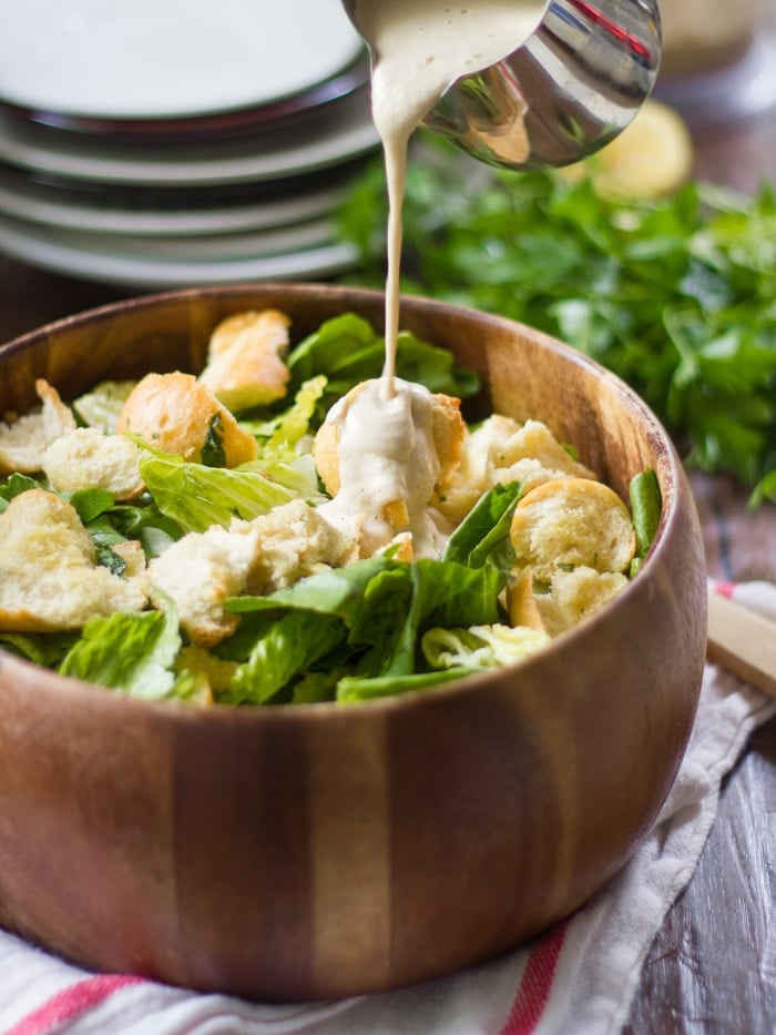 Vegan Caesar Salad in a Wooden Bowl with Dressing Being Poured on Top