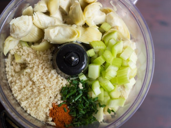 Food Processor Bowl Filled with Artichoke Hearts, Celery, Panko Breadcrumbs and Seasonings for Making Vegan Crab Cakes