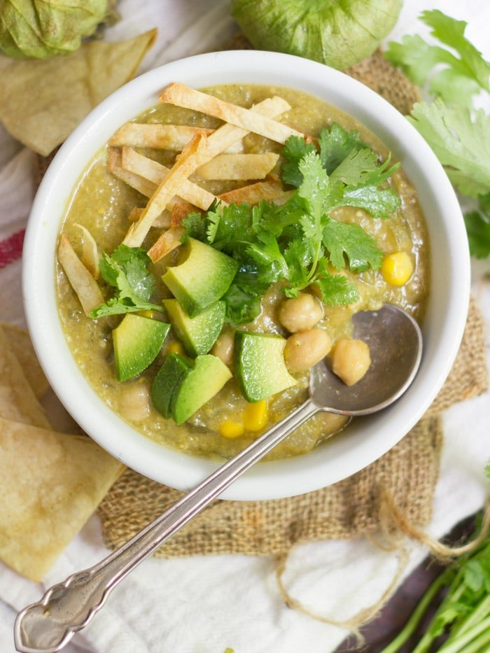 Bowl of Chickpea Chile Verde Topped with Avocado Chunks, Tortilla Strips, and Cilantro