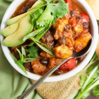 Overhead View of a Bowl of Plantain Chili Topped with Avocado Slices and Cilantro