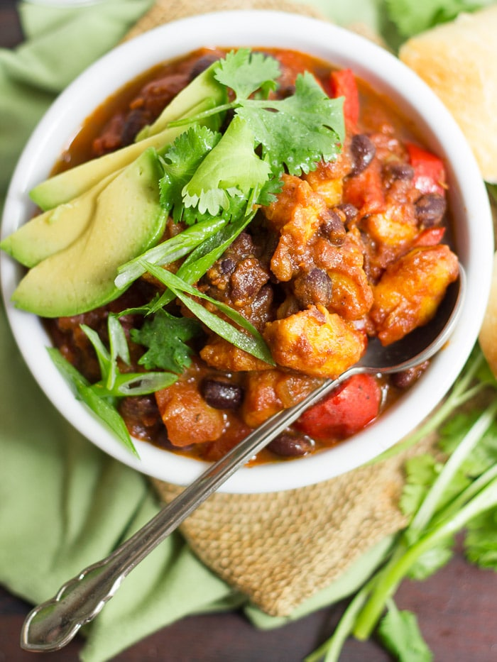 Overhead View of a Bowl of Black Bean Plantain Chili with Spoon, Avocado Slices, and Fresh Herbs