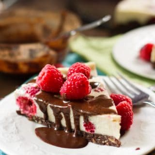 Slice of Raw Vegan Cheesecake on a Plate, Topped with Chocolate Sauce and Raspberries