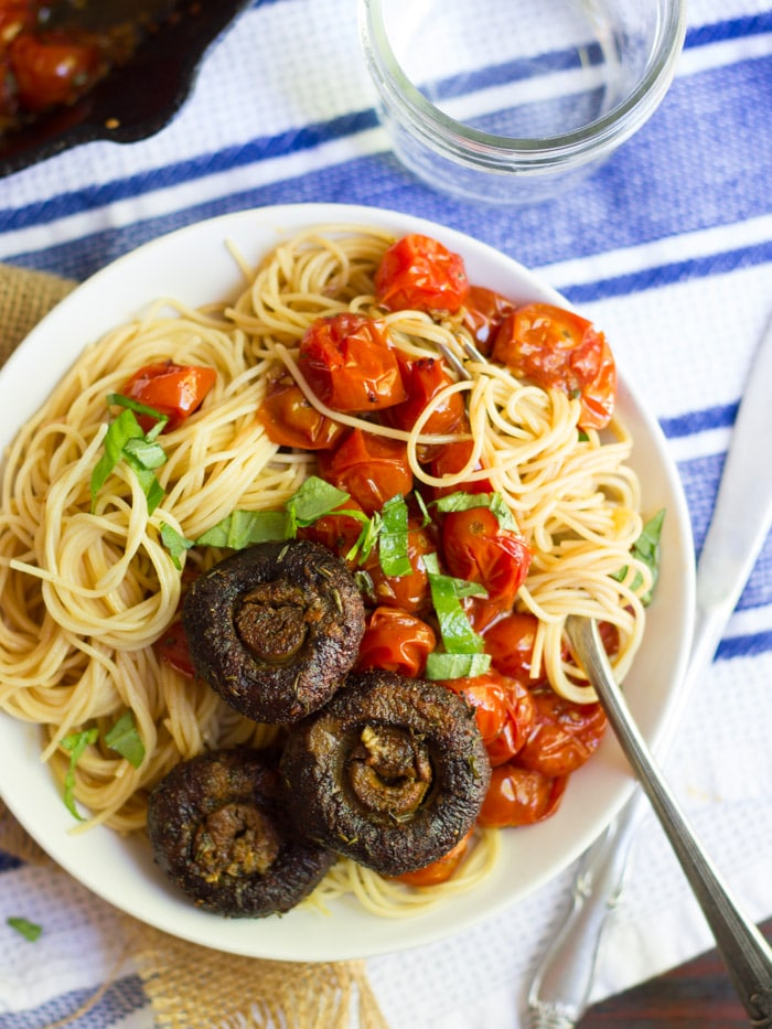 Bowl of Capellini and Mushrooms with Cherry Tomato Sauce with Cluster of Pasta Wrapped around a Fork