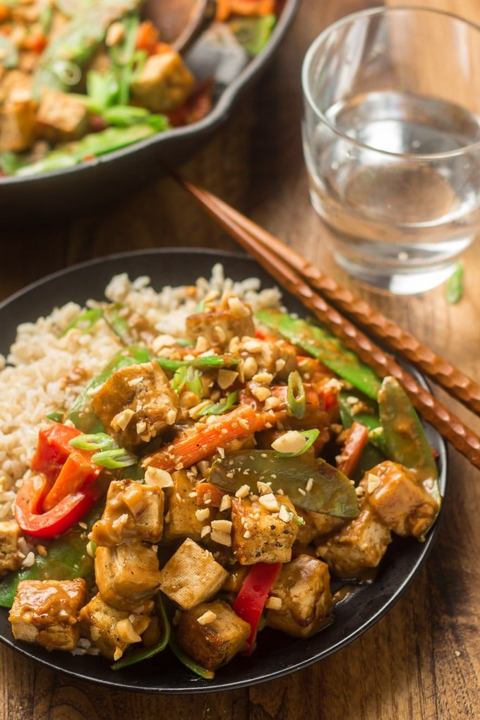 Plate of Peanut Butter Tofu Stir-Fry and Rice with Skillet and Water Glass in the Background