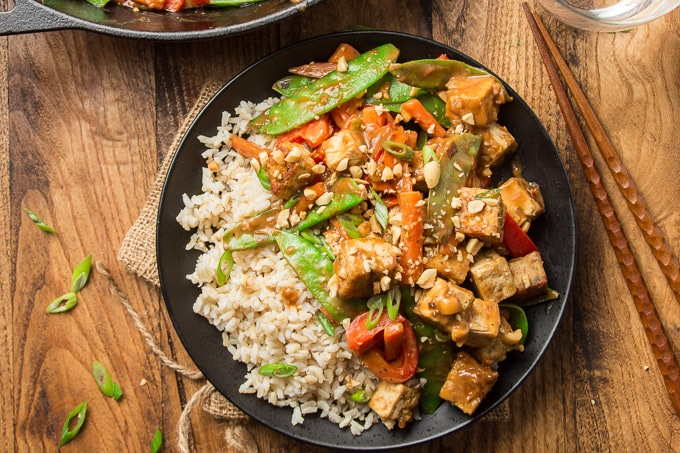 Plate of Peanut Butter Tofu Stir-Fry with Chopsticks on a Wooden Surface