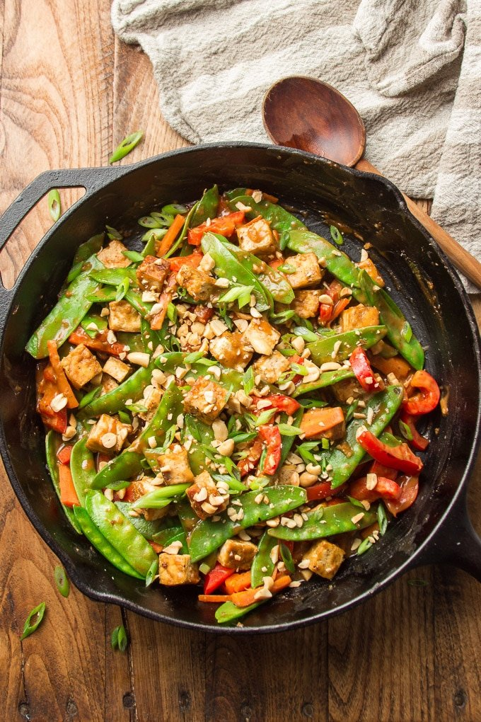 Cast Iron Skillet Filled with Peanut Butter Tofu Stir-Fry on a Wooden Table
