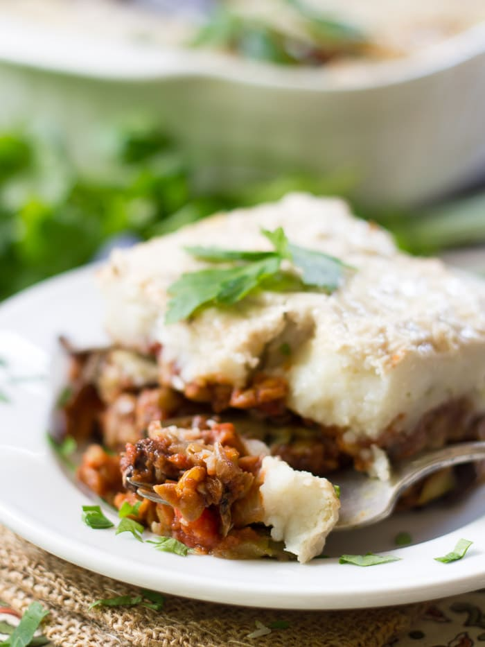 Vegan Eggplant Moussaka on a Plate with a Bite Removed by a Fork